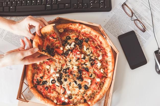 Pizza vegetariana na mesa de escritório