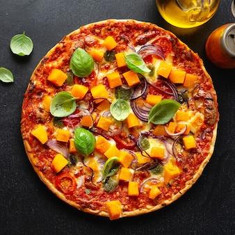 Pizza vegetariana outonal com abóbora e legumes em fundo escuro. quadrado.
