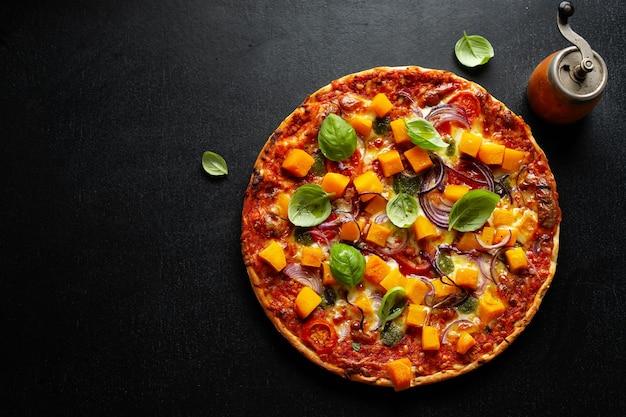 Pizza vegetariana outonal com abóbora e legumes em fundo escuro.