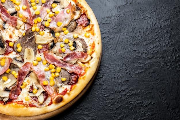 Pizza viennesa em fundo preto, à base de tomate com mussarela, vitela, filé de frango, bacon, salame napoli, milho e cogumelos em uma bancada de madeira