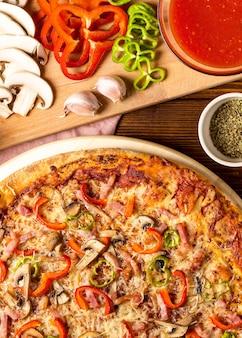 Pizza vista de cima com pimenta vermelha e molho de tomate