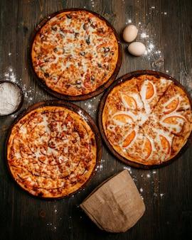 Pizza vista frontal com queijo no chão rústico de madeira