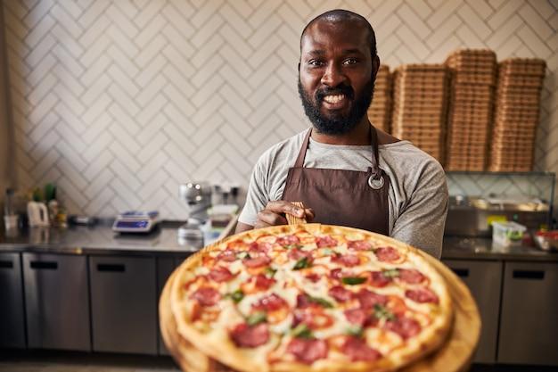 Pizzaiolo masculino alegre de avental olhando para a câmera e sorrindo enquanto segura uma deliciosa pizza de pepperoni