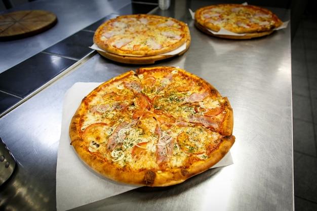 Pizzas coloridas em fatias com queijo mussarela, frango, milho doce, pimentão e orégano