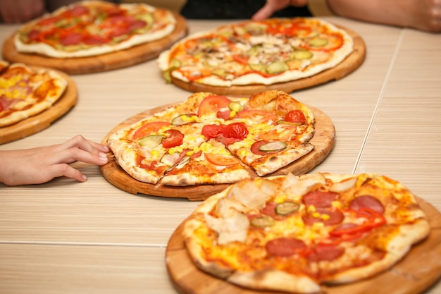 Pizzas coloridas em fatias com queijo mussarela, frango, milho doce, salame doce e tomate