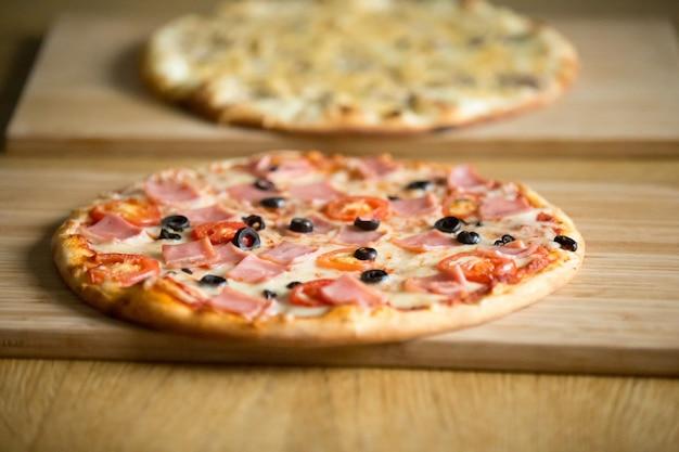 Pizzas italianas em tábuas de madeira na mesa do restaurante, conceito de pizzaria