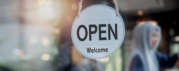 Placa aberta na frente da porta do café e da loja, novo conceito normal e inicie o negócio durante o coronavírus ou covid-19