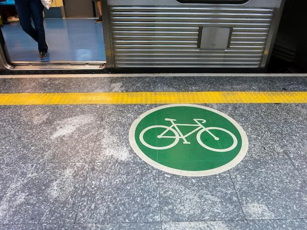 Placa adesiva no chão indicando área de acesso de bicicleta no metrô brasileiro