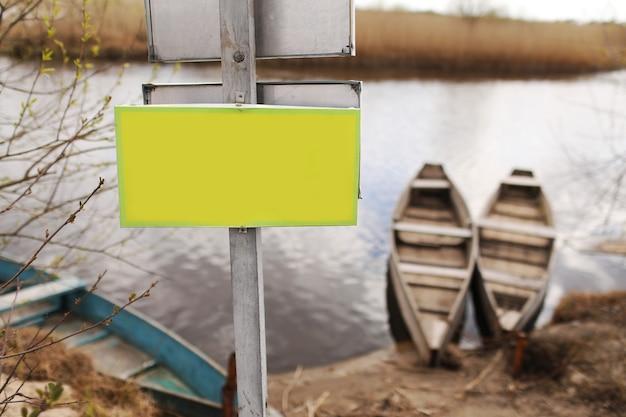 Placa amarela para inscrição na grama à beira do rio e fundo de barcos no início da primavera.