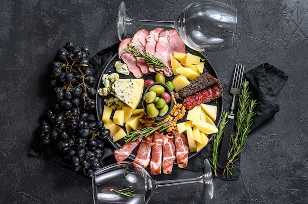 Placa antepasto com carne fatiada, presunto, salame, queijo, azeitonas. parede preta. vista do topo