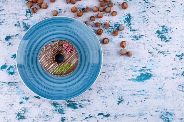 Placa azul com donut de chocolate e avelãs sem casca na superfície branca.