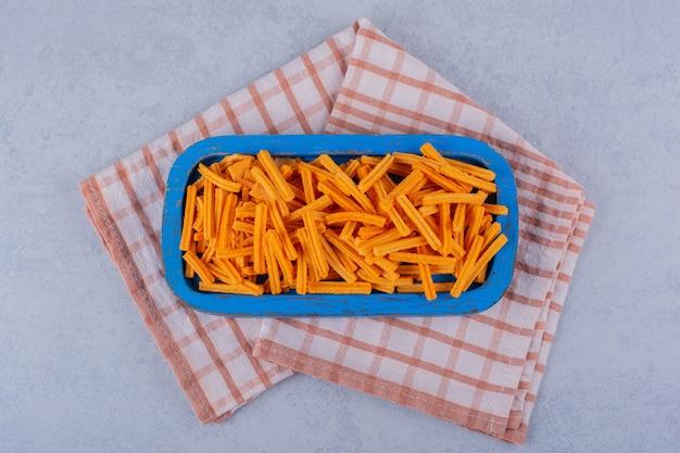 Placa azul de batatas fritas crocantes na mesa de pedra.