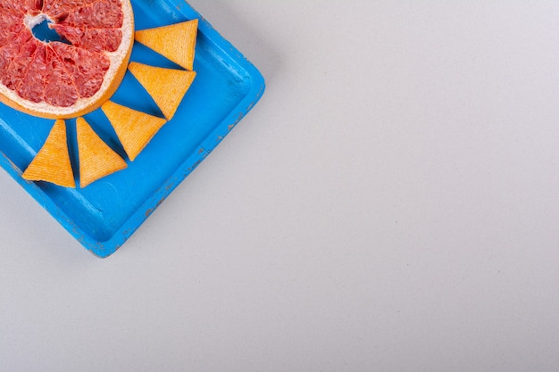 Placa azul de chips de triângulo e fatia de toranja em fundo branco. foto de alta qualidade