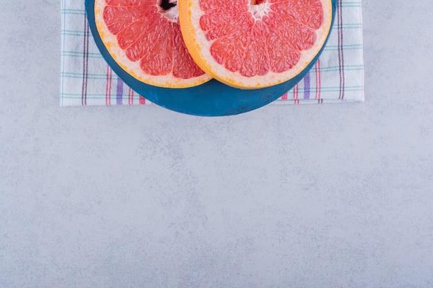 Placa azul de fatias de toranja fresca na mesa de pedra.