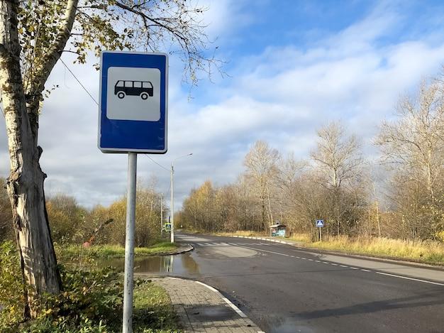 Placa azul de parada de ônibus ao lado da estrada