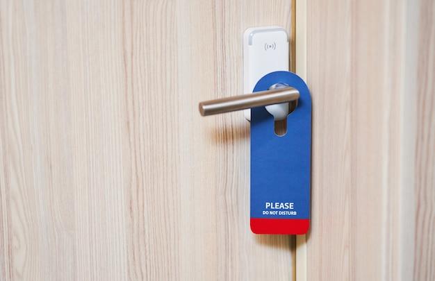 Placa azul pendurada na maçaneta da porta de um quarto de hotel