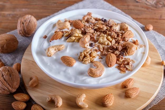 Placa branca com iogurte grego, granola, amêndoa, caju, nozes em madeira marrom.