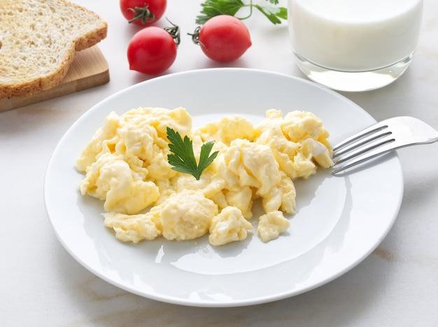 Placa branca com os ovos mexidos fritos em um fundo da luz branca com tomates. omelete