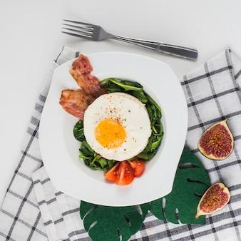 Placa branca de ovos fritos; espinafre; tomates e bacon sobre o fundo branco com guardanapo e garfo