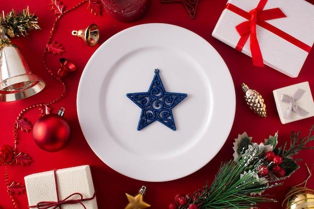 Placa branca e enfeite de natal na superfície vermelha. conceito de jantar de natal.