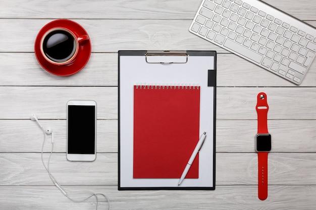 Placa branca mesa pasta vermelho notepad xícara de café relógio teclado processo de trabalho