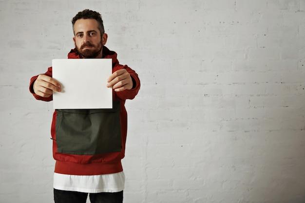 Placa branca simples segurada por um modelo masculino bonito e atraente com barba vestindo uma jaqueta vermelha e cinza, jeans e uma camiseta branca isolada no branco
