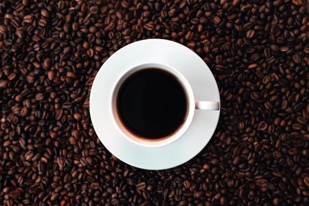 Placa branca, xícara de café em um monte de fundo de grãos de café torrados. foto de alta qualidade
