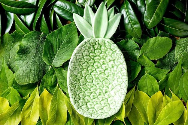 Placa cerâmica abacaxi verde em fundo feito de folhas verdes diferentes, gradiente de verde. copie o espaço. layout criativo da natureza, vista superior, disposição plana. conceito de comida ecológica