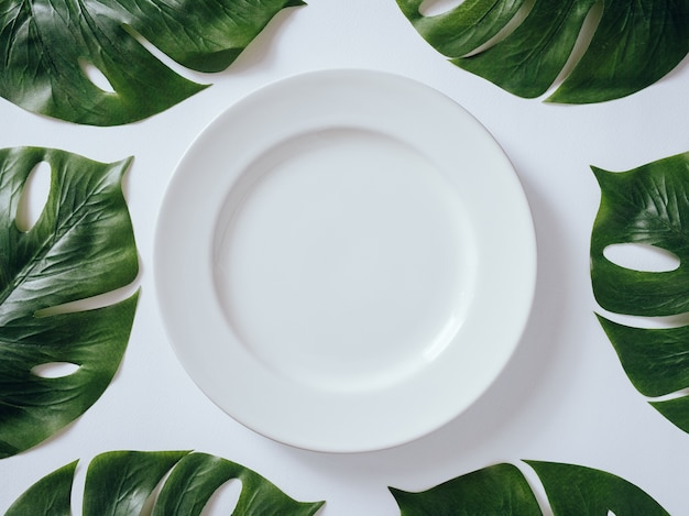 Placa cerâmica branca com as folhas tropicais monstera no fundo branco.