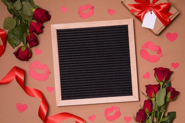 Placa clara da letra no fundo do dia de valentim com rosas vermelhas, beijos e corações.