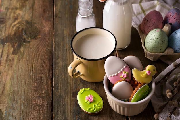 Placa com biscoitos de páscoa coloridos e copo de leite, estilo rústico