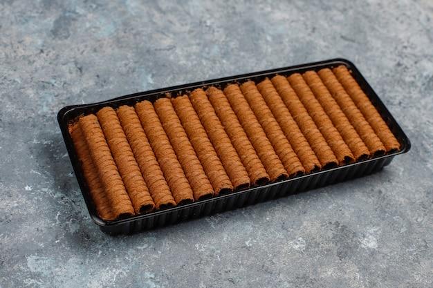 Placa com bolacha saborosa roll varas na superfície de concreto