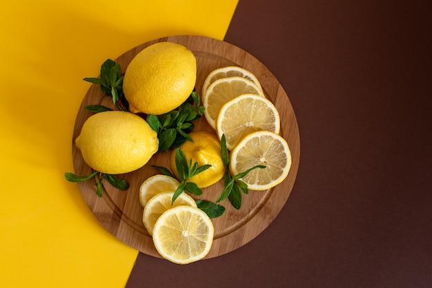 Placa com corte de limões e raspas na mesa de madeira, closeup