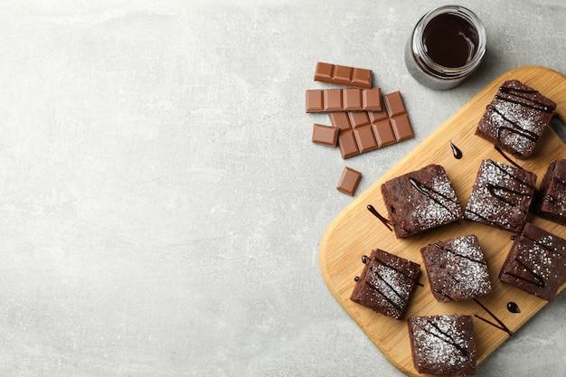Placa com fatias de bolo de chocolate e chocolate no fundo cinza, espaço para texto