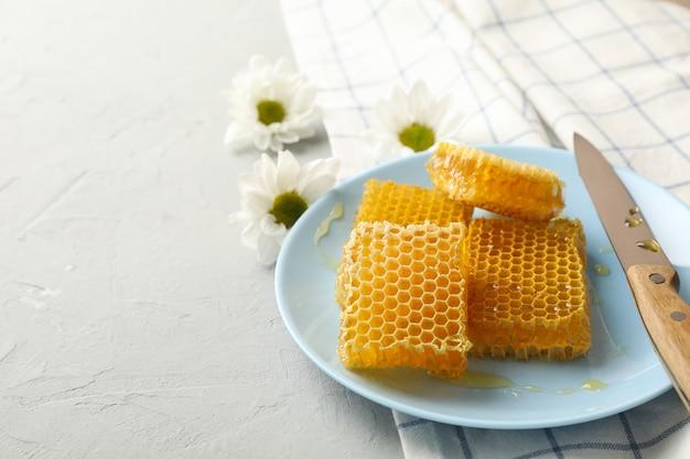 Placa com favos de mel e faca no fundo branco