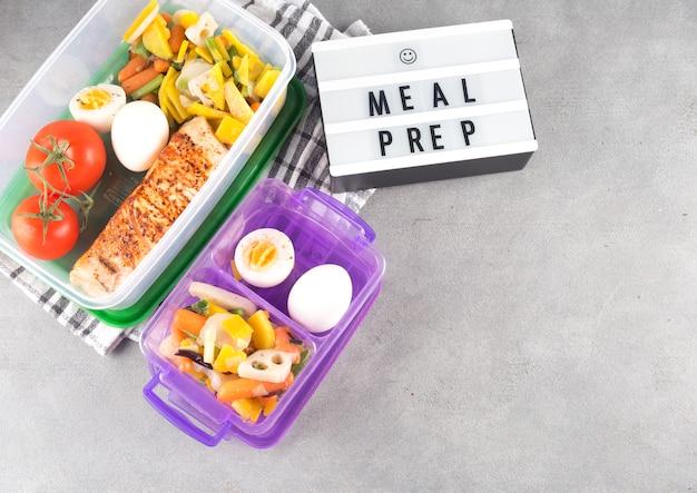 Placa com inscrição de preparação refeição perto de alimentos em recipientes