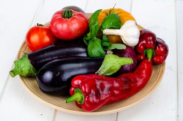 Placa com legumes maduros brilhantes na mesa de madeira branca. foto do estúdio. Foto Premium