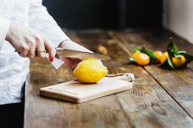 Placa com limão e limão para cortar, preparando-se para cozinhar, saladas e aperitivos, suco de limão, decorar pratos, cozinhar, homem cortando um limão, segurando uma faca de cozinha na mão, cortando um limão