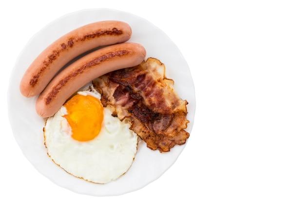 Placa com ovos fritos, bacon e salsichas em fundo branco. copie o espaço.