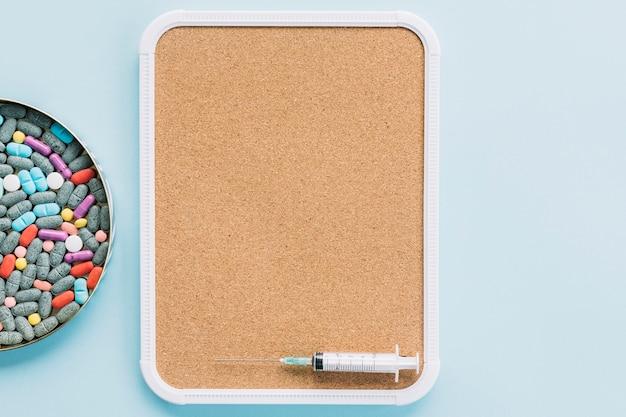 Placa com pílulas coloridas e seringa na bandeja de cortiça contra pano de fundo azul