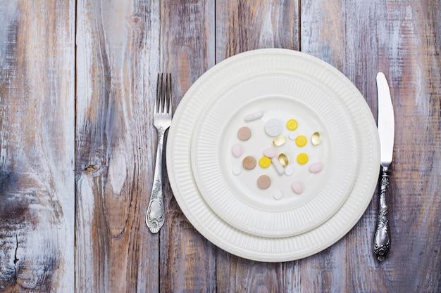 Placa com pílulas na mesa de madeira