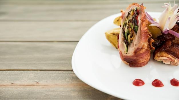 Placa com rolo de carne assada e fatias de batata na mesa de madeira