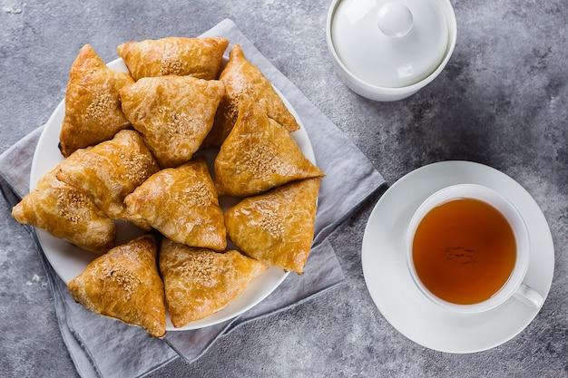 Placa com samsa delicioso dos samosas com carne no fundo cinzento, vista superior. comida uzbeque