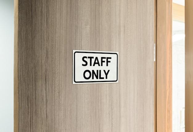 Placa de advertência em aço inoxidável prateado com mensagem pessoal em preto na frente da porta de madeira