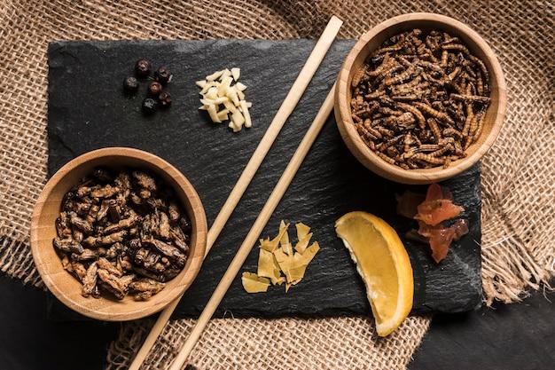 Placa de ardósia com insetos e especiarias