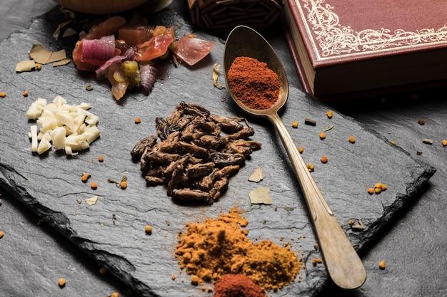 Placa de ardósia com insetos fritos e especiarias