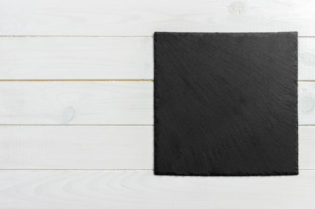 Placa de ardósia em fundo de madeira, espaço para escrever texto
