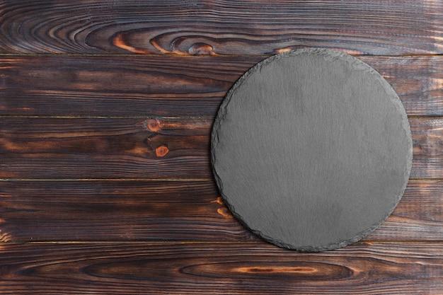 Placa de ardósia natural redonda. suporte cinzento escuro da ardósia na superfície de madeira.