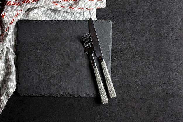 Placa de ardósia preta com garfo e faca e toalha de mesa