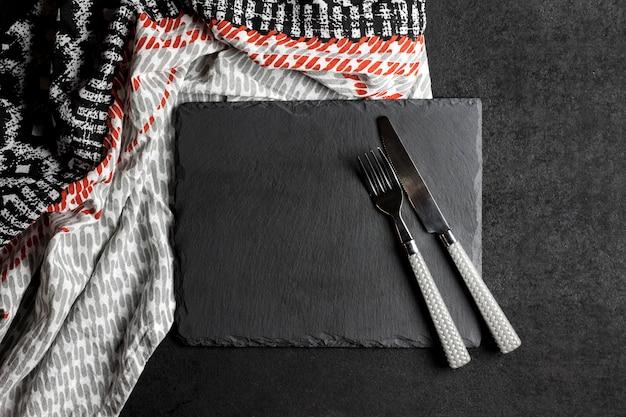 Placa de ardósia preta com garfo e faca na superfície preta e toalha de mesa. configuração de mesa.